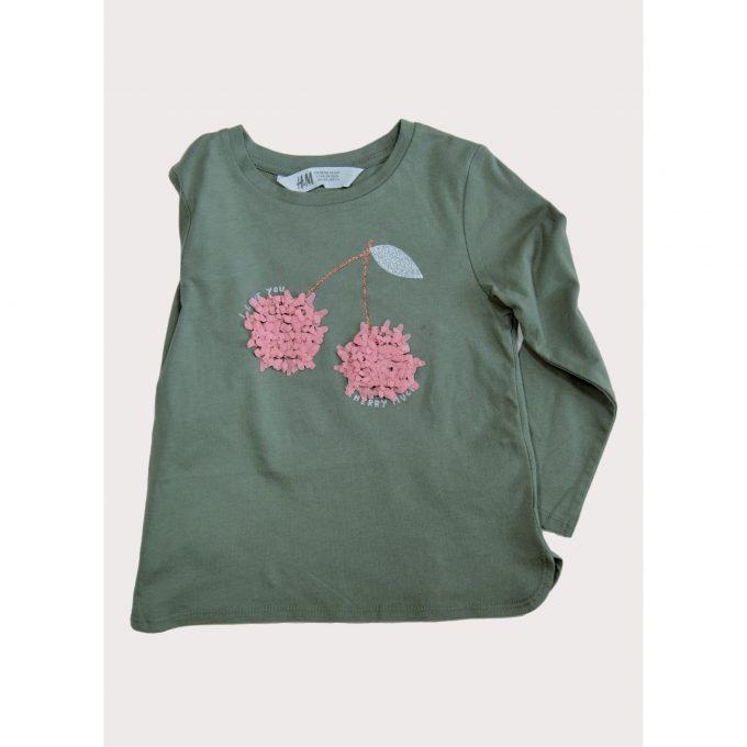 Bild von Kinder T-shirt für Mädchen. Das T-Shirt ist grün mit zwei Schneeball-Blüten in Pink. Second Hand Ware für das Projekt Carla Caritas Steiermark