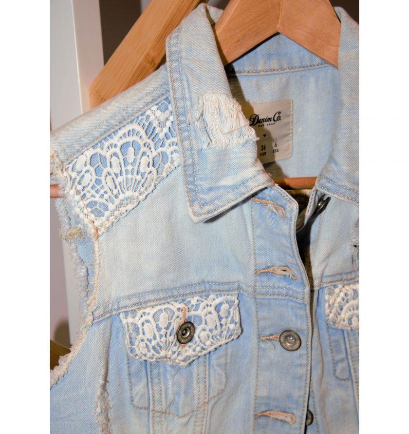 Bild von einer Jeansjacke für Damen. Aermellos -Marke: Denim Co. Hellblau mit Spitze auf den Schultern, den Brusttaschen und am Ruecken. Destroyed-Details und Knopfleiste. Second Hand - Projekt Carla Styria