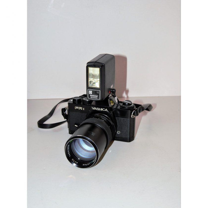 Bild von einer Rollfilmkamera. Yashica FR-I mit Objektiv Yashica Yashinon 135mm/ f2,8 und Aufsteckblitz National PE 2002. Schwarz mit weiß verzierten Gravuren. Projekt Carla Styria