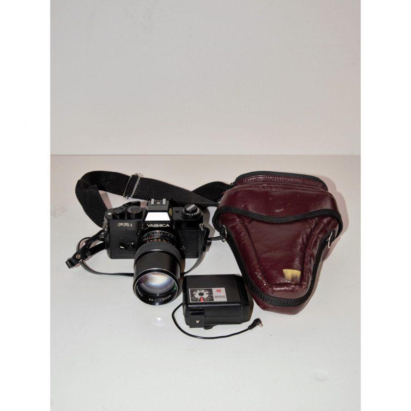 Bild von einer Rollfilmkamera. Yashica FR-I mit Objektiv Yashica Yashinon 135mm/ f2,8 und Aufsteckblitz National PE 2002. Schwarz mit weiß verzierten Gravuren. Mit Tasche im dunklen rot. Projekt Carla Styria